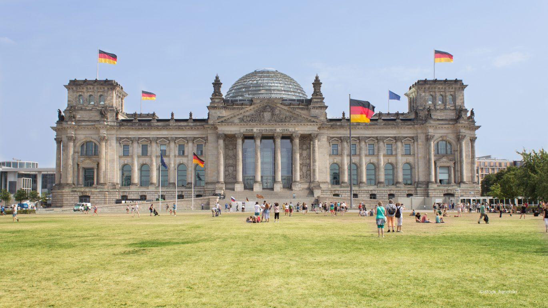 Reichstag in Berlin mit vielen Menschen auf der Wiese vor dem Gebäude.