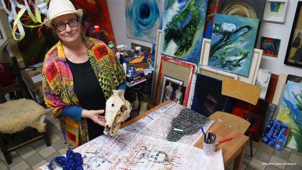 Hanna Mauermann steht in ihrem Atelier und zeigt ihre Kunst.