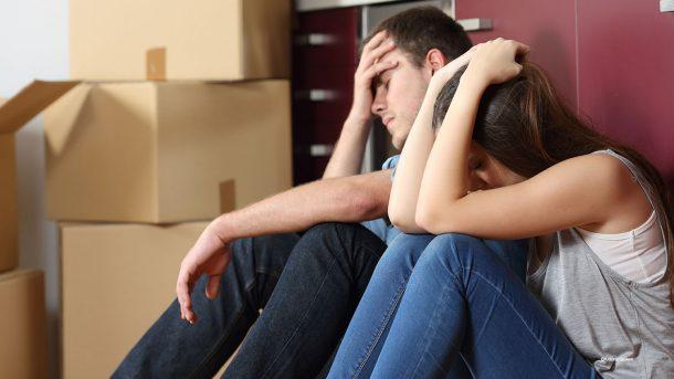 Junger Mann und junge Frau sitzen neben Umzugskartons und sehen verzweifelt aus.