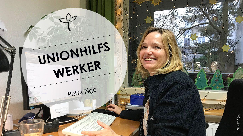 Petra Ngo an ihrem Schreibtisch, auf dem ein Rechner mit Tastatur steht.