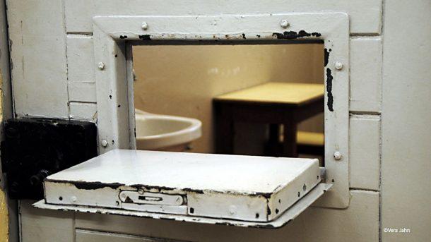 Die geöffnete Klappe einer Gefängnistür zeigt den Blick eine Zelle. .