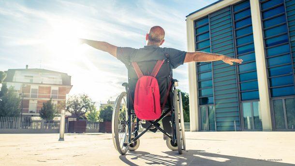 Ein Mann im Rollstuhl von hinten, der beide Arme ausstreckt. Die Sonne strahlt ihn an.