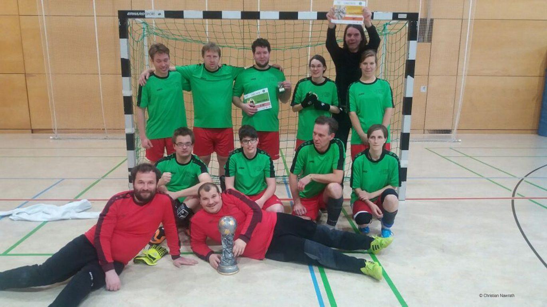 Gruppenbild der Fussballer vor dem Tor und mit Pokal.