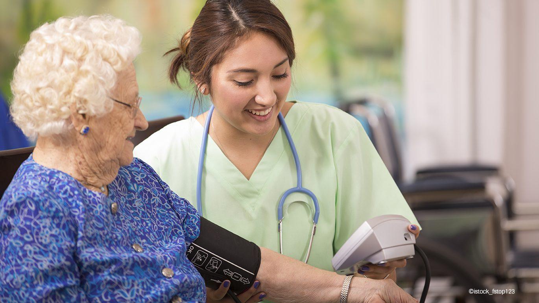 Junge Krankenschwester mißt den Blutdruck bei einer Seniorin.