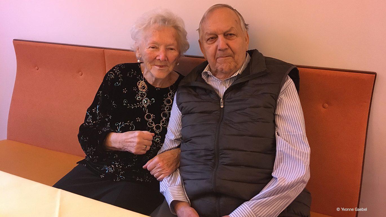Senior und Seniorin gemeinsam auf einer Sitzbank