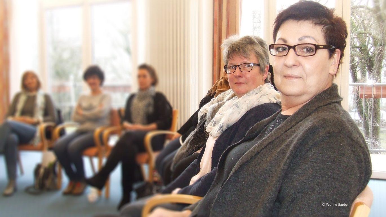 Zwei Frauen nehmen an einem Seminar teil und sitzen in einem Stuhlkreis mit weiteren Teilnehmerinnen