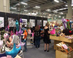 Viele bunte Produkte der USE bei der Werkstatt-Messe, zum Beispiel Kissen, Bilder, Taschen